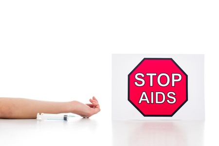 cropped shot of dead body with empty syringe lying near stop aids banner isolated on white