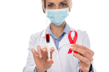 close-up shot of female doctor with syringe and aids ribbon isolated on white Stock Photo