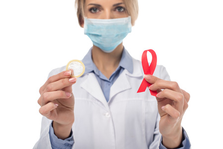 young female doctor with aids ribbon and condom isolated on white Stock Photo