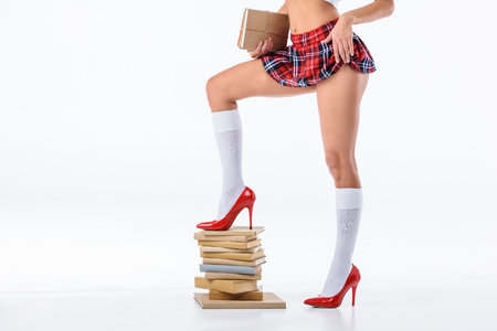 cropped shot of sexy schoolgirl standing on stack of books isolated on white Banque d'images