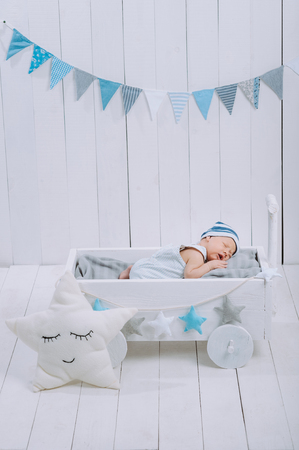 cute newborn baby in hat sleeping in wooden baby cot with star pillow near by Stock Photo
