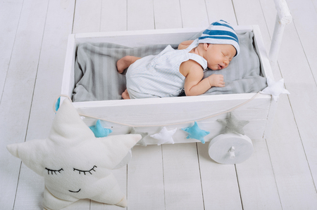 high angle view of cute newborn baby sleeping in wooden baby crib Archivio Fotografico