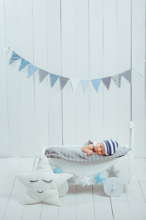 innocent little infant baby lying in wooden baby cot Stock Photo