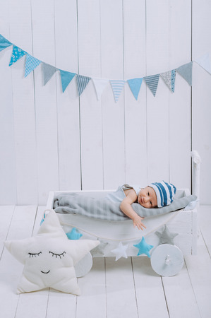 innocent little infant baby lying in wooden baby cot Archivio Fotografico