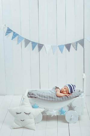 adorable infant baby in hat resting in wooden baby crib decorated with stars Stock Photo