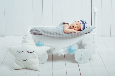 portrait of adorable infant baby in hat sleeping in wooden baby cot decorated with stars Imagens