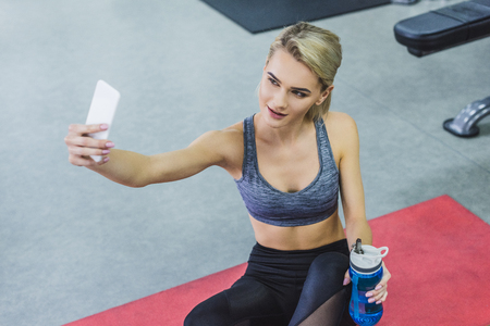 high angle view of young smiling woman taking selfie while training