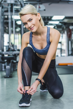 young sportive woman lacing up sneakers before training at gym