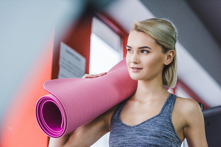 beautiful young woman with rolled yoga mat at gym Stock fotó - 114470407