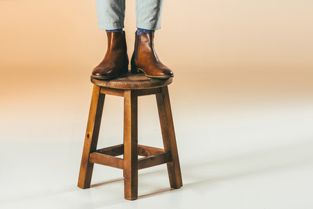 cropped shot of man standing on wooden chair Banque d'images