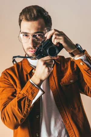 portrait of fashionable young man in eyeglasses with photo camera, isolated on beige