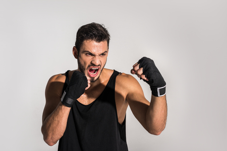 agressive screaming fighter with bandaged hands isolated on grey