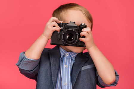 obscured view of kid holding photo camera isolated on pink Stock Photo