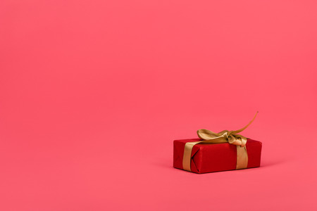 close up view of wrapped gift with ribbon isolated on pink