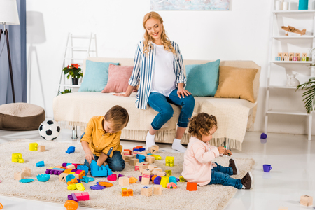 happy pregnant mother looking how children playing with toys