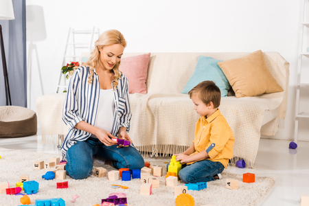 pregnant mother playing plastic blocks with son