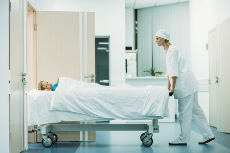 side view of doctor moving preschooler patient on medical stretcher in corridor Stockfoto