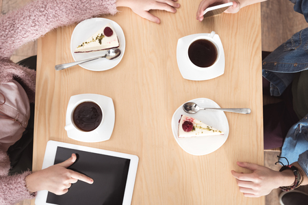 cropped image of children sitting at table with gadgets on surface at cafe Stock Photo