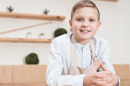 smiling boy in apron looking at camera while leaning on table at cafe Stock Photo