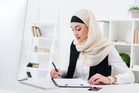 portrait of focused muslim businesswoman signing papers at workplace Stock Photo