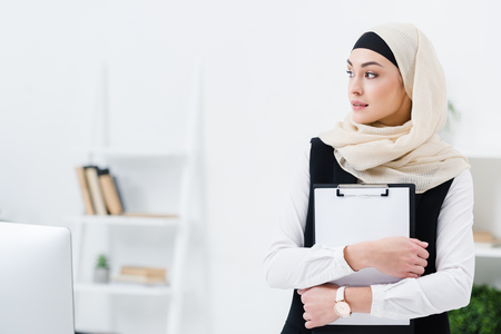 portrait of thoughtful arabic businesswoman with folder in hands in office