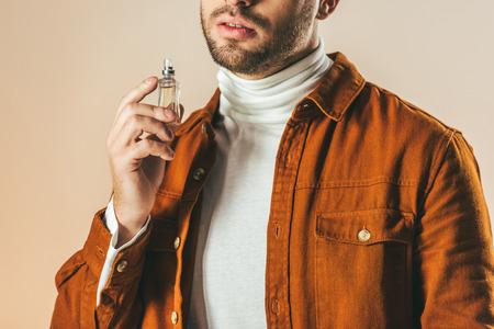 cropped shot of stylish man applying perfume isolated on beige Stock fotó