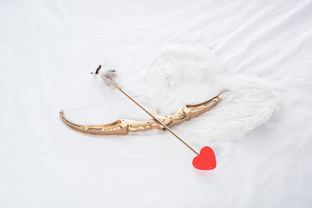 top view of wings, bow and arrow on white bed Standard-Bild