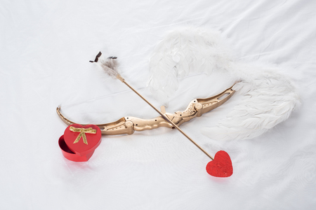 top view of gift box, wings, bow and arrow on white bed