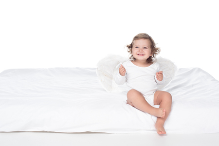 adorable happy baby with wings sitting on bed, isolated on white Stock fotó