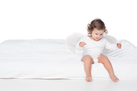 adorable happy baby with wings sitting on bed, isolated on white Banco de Imagens