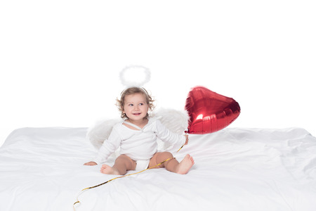 little angel with wings and nimbus holding red heart balloon, isolated on white