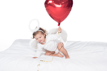 little angel with wings and nimbus holding heart balloon, isolated on white