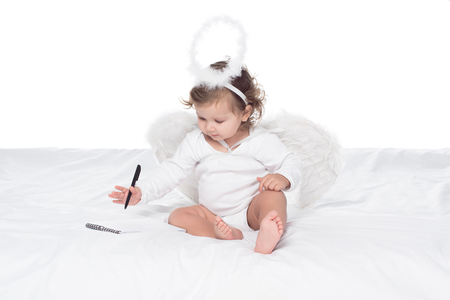 little angel with wings and nimbus writing in notepad on bed, isolated on white