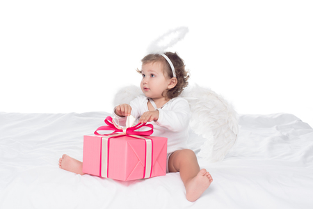 little angel with nimbus sitting on bed with gift boxes, isolated on white Banco de Imagens