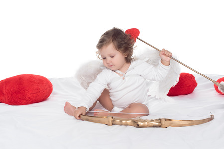 little cherub sitting on bed with bow and arrow, isolated on white