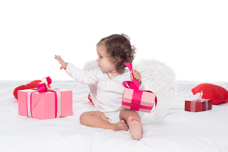 cute baby angel sitting on bed with presents, isolated on white Banco de Imagens