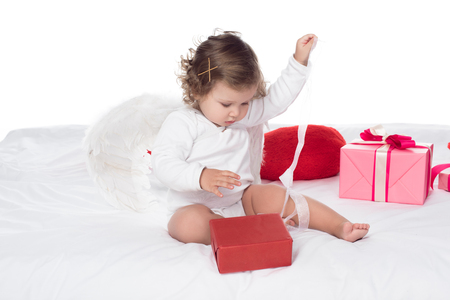 little angel sitting on bed with gift boxes, isolated on white Foto de archivo - 114470741
