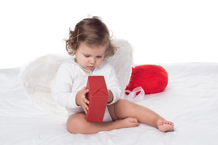 little cherub with wings holding gift on bed, isolated on white