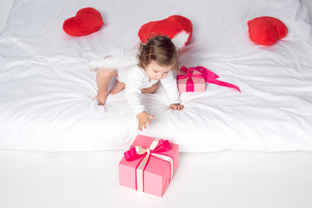 little cherub with wings on bed with hearts and presents