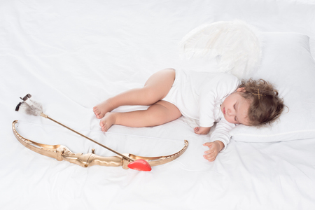 little angel with wings lying on bed with bow and arrow