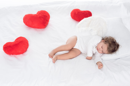 little angel with wings lying on bed with hearts