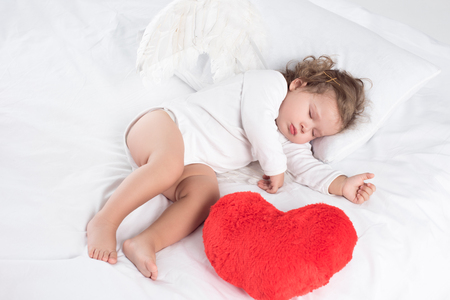 little baby with sleeping on bed with heart, isolated on white