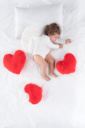 little cupid with wings lying on bed with red hearts