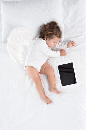 little baby sleeping on bed with digital table Stok Fotoğraf - 114471091