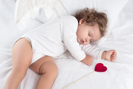 cute cherub with wings lying on bed with heart Banco de Imagens