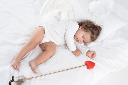 little cupid with wings sleeping on bed with arrow 스톡 콘텐츠