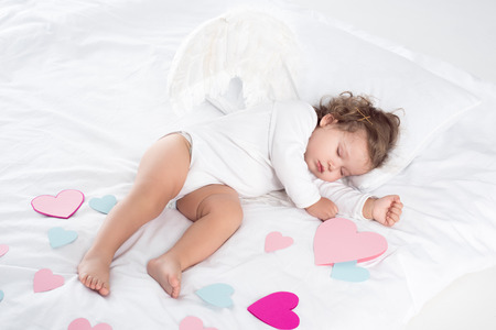 little cherub with wings sleeping on bed with hearts Reklamní fotografie