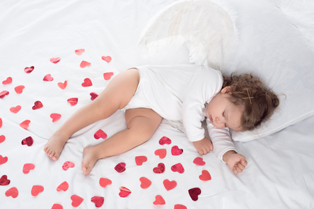 little cupid with wings sleeping on bed with red hearts Standard-Bild