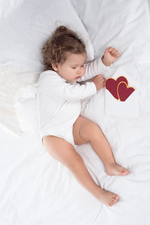 little cherub with wings lying on bed with hearts
