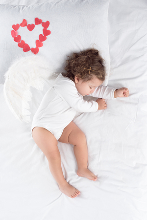 adorable cupid with wings sleeping on bed with red hearts Foto de archivo